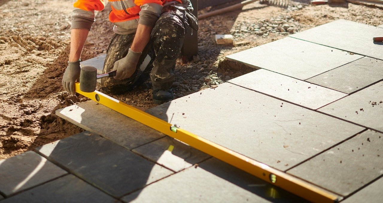 professional-showing-how-to-lay-porcelain-paving-min.jpg